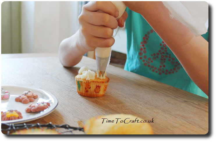 piping fondant onto cupcake childs baking activity