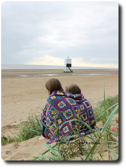 sisters on the beach with crochet blanket