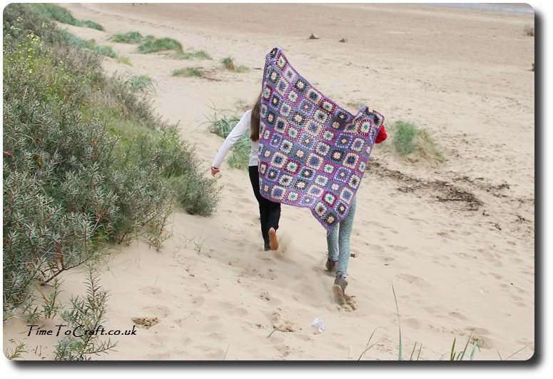 sisters running on the beach with crochet blanket