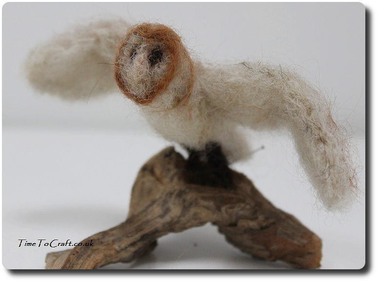 needlefelted barn owl flying on branch
