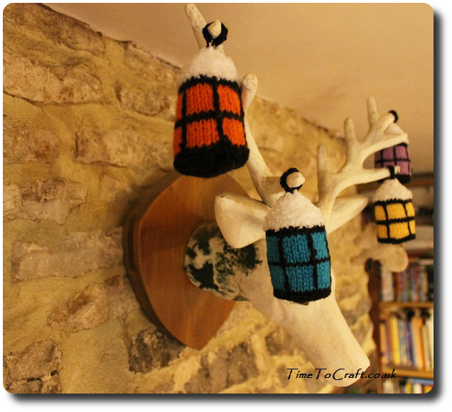 knitted multicolour Christmas lanterns with snow close