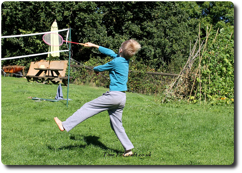 T playing badminton in the garden